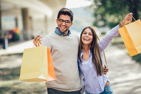 Retrato de pareja feliz con bolsas de la compra después de ir de compras en la ciudad sonriendo y sosteniendo una tarjeta de crédito