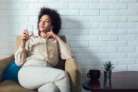 Joven y bella mujer afroamericana relajante en casa, bebiendo vino.