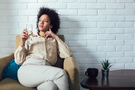 Young beautiful african american woman relaxing at home, drinking wine.