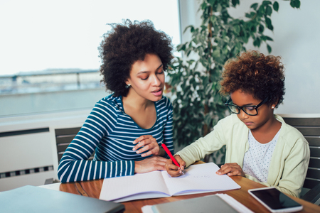 Mother and daughter doing homework learning to calculate Stock Photo