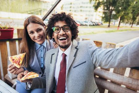 Felice giovane squadra di affari che mangia pizza in caffè all'aperto fare selfie foto.Affari,cibo e concetto di persone.