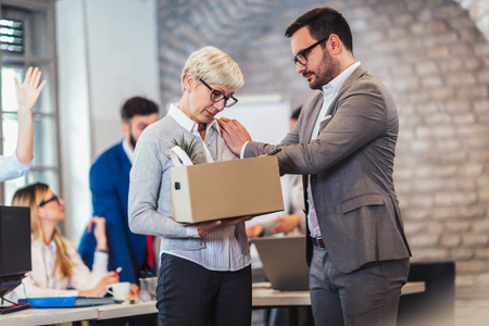 Elderly employee leaving office with box full of belongings. Time to retire