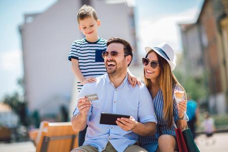Padres sonrientes y niño con tablet pc y tarjeta de crédito al aire libre