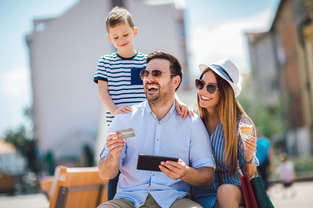 Smiling parents and little boy with tablet pc and credit card outdoor