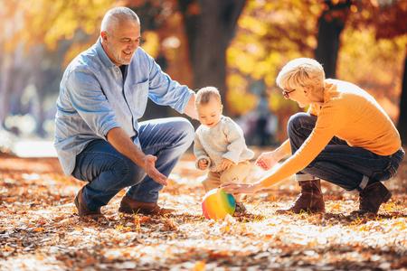 Abuelos y nieto juntos en el parque otoño Foto de archivo