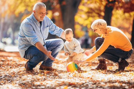 Grandparents and grandson together in autumn park Foto de archivo