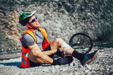 The biker fell from a bike, using a bandage from his first aid kit to help himself. Bicycle accident.