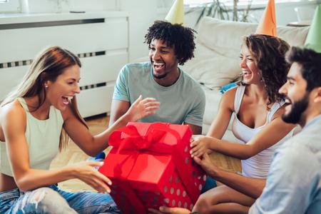 Amigos celebrando un cumpleaños y dando un regalo a una chica en la fiesta de casa Foto de archivo