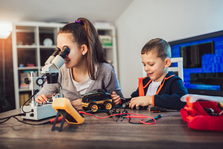 Happy smiling boy and girl constructs technical toy and make robot. Technical toy on table full of details