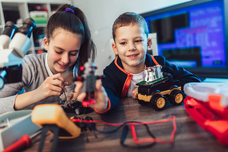 Happy smiling boy and girl constructs technical toy and make robot. Technical toy on table full of details Standard-Bild
