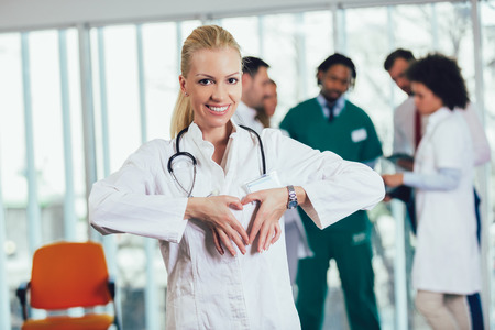 Portrait of a female doctor showing heart gesture with hands Stock Photo