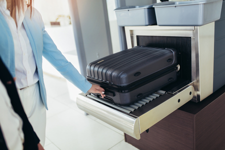 Business travelers put baggage on X-ray machine try to detection metal prevention at the airport before take off 写真素材 - 122311313