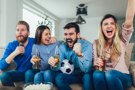 Happy friends or football fans watching soccer on tv and celebrating victory at home.Friendship, sports and entertainment concept. Фото со стока