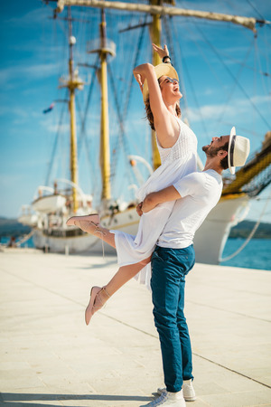 Happy young couple walking by the harbor of a touristic sea resort with sailboats on background Фото со стока - 122311928