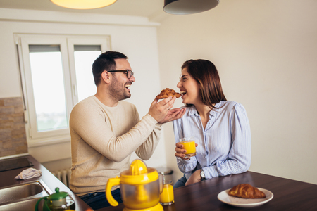 Happy young couple in the kitchen breakfast together