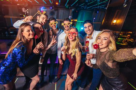 Group of friends partying in a nightclub make selfie photo Standard-Bild - 122886687