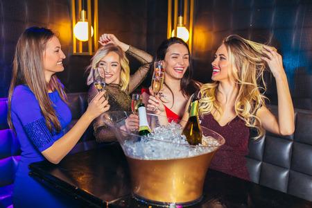 Mujeres felices tintineando copas de champán y celebrando en el club nocturno Foto de archivo