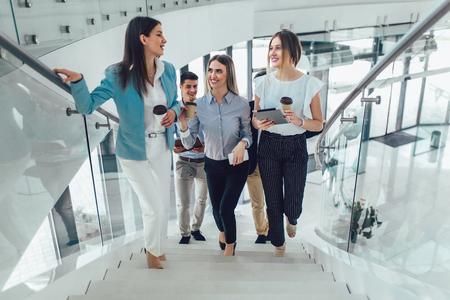 Groep zakenlieden en zakenvrouwen die lopen en trappen nemen in een kantoorgebouw Stockfoto