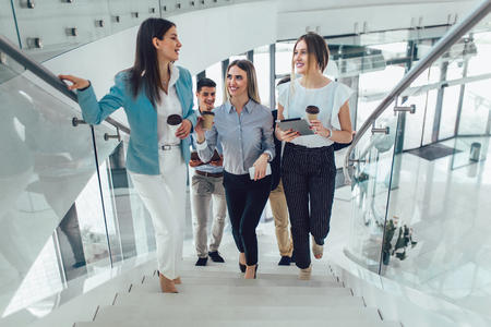 Group of businessmen and businesswomen walking and taking stairs in an office building Banque d'images