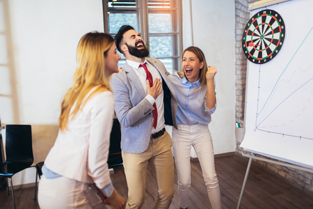 Business people making team training exercise during team building seminar, play darts. Indoor team building activities.
