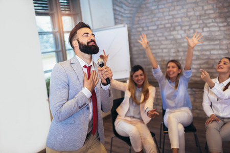 Business people making team training exercise during team building seminar singing karaoke. Indoor team building activities Stock Photo