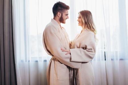 Joven pareja feliz en la habitación del hotel por la mañana. Hombre y mujer recién casados de pie en la ventana. Foto de archivo