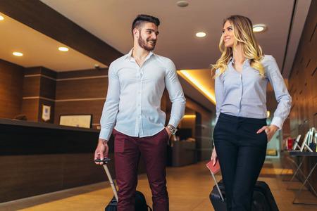 호텔의 리셉션 데스크 근처에 있는 젊은 부부. 호텔을 떠나는 젊은 부부