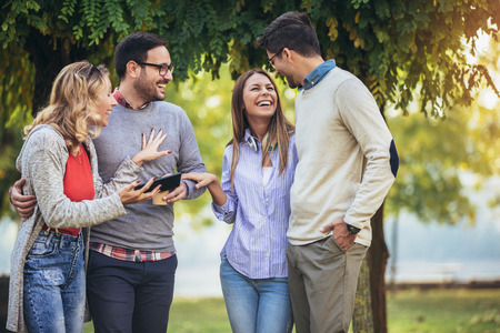 Four happy smiling young friends walking outdoors in the park holding digital tablet Foto de archivo
