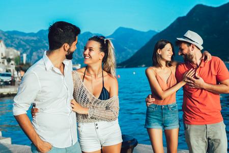 Vrienden wandelen door de haven van een toeristische badplaats met boten op de achtergrond