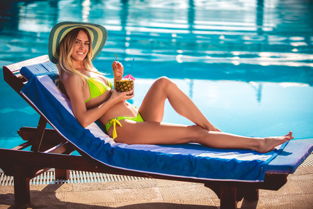 Portrait of young woman with cocktail chilling in the tropical sun near swimming pool on a deck chair