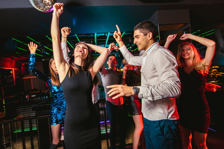 Young happy people are dancing in club. Nightlife and disco concept. Stock Photo