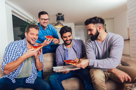 Group of four male friends eating pizza at home. Stock Photo