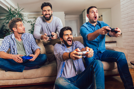 Smiling male friends playing video games at home and having fun. Imagens - 124758395