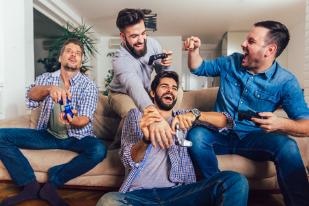 Smiling male friends playing video games at home and having fun. Imagens - 124758396