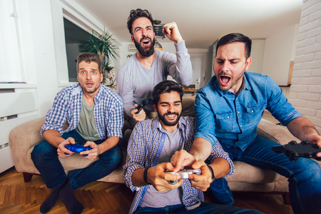 Smiling male friends playing video games at home and having fun. Imagens - 124758397