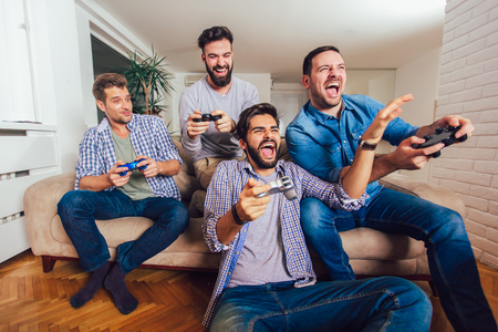 Smiling male friends playing video games at home and having fun.