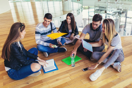 Fellow students sitting on floor in campus and preparing together for exams Фото со стока