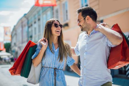 Beautiful young couple enjoying in shopping, having fun in the city