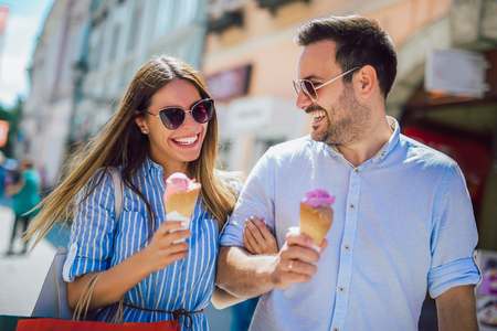 Happy couple having date and eating ice cream after shopping
