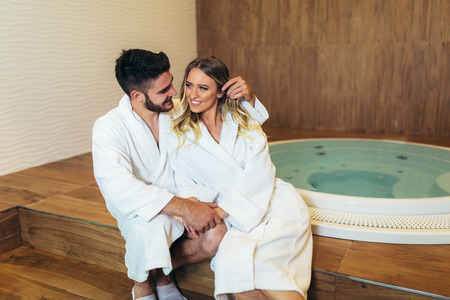 Happy young couple enjoying treatments and relaxing at wellness spa center