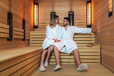 Healthy beautiful couple relaxing in infrared sauna during wellness weekend