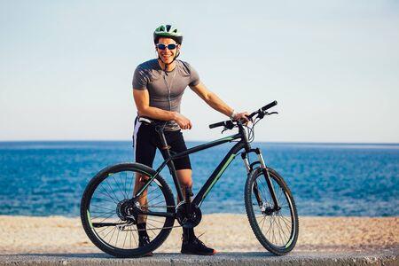 L'homme fait du vélo de montagne sur la plage. Concept de sport et de vie active.