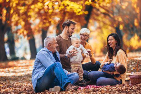 Familia de generación múltiple en otoño parque divirtiéndose