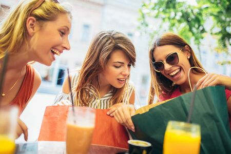 Drie jonge vrouwen in een café na het winkelen Stockfoto