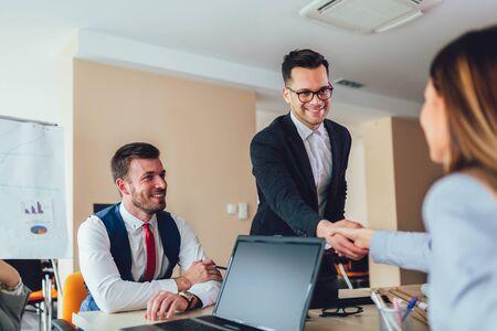 Geschäft, das einem Kunden im Büro die Hand schüttelt