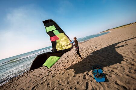 Handsome Caucasian man professional surfer standing  on the sandy beach with his kite Stok Fotoğraf