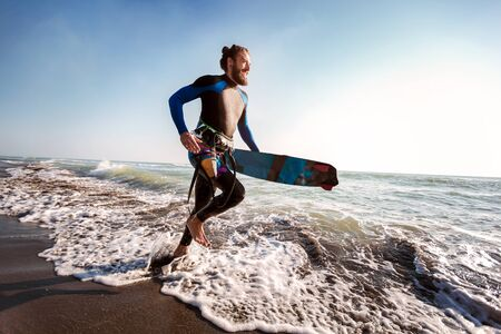 Portrait of surfer man with surf board on the beach. Summer sport activity