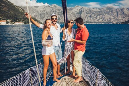 Smiling friends sailing on yacht - vacation, travel, sea, friendship and people concept Zdjęcie Seryjne