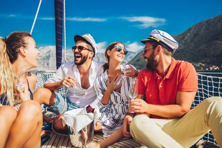 Smiling friends with glasses of champagne on yacht. Vacation, travel, sea, friendship and people concept