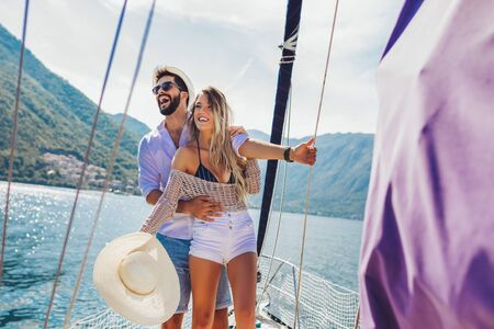 Loving couple spending happy time on a yacht at sea. Luxury vacation on a seaboat.